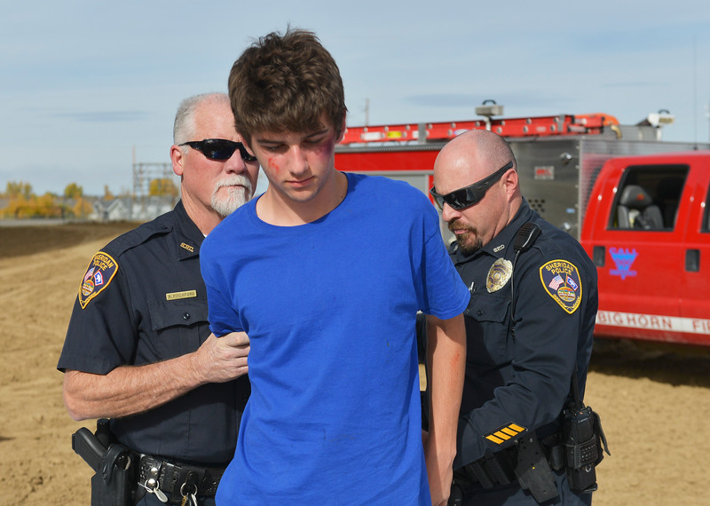 Justin Sheely | The Sheridan Press<br /> Tongue River High School student Jaren Fritz is arrested after failing a field sobriety test by Sheridan Police Officers during the Last Call Demonstration Wednesday at the Sheridan County Fairgrounds. Tongue River seniors Sierra McCoy and Kylee Knobloch organized the demonstration for their FCCLA project. Students from Big Horn and Tongue River high schools participated in role playing a scenario of students driving after an underage drinking party collides head-on with another vehicle full of students returning home from a day hiking in the Tongue River Canyon. The scenario was to graphically demonstrate to the student body from Big Horn and Tongue River high schools, the consequences of drunken and distracted driving. Sheridan Fire-Rescue helped organized the demonstration. Agencies in the demonstration included Sheridan County Sheriff's Office, Big Horn and Tongue River Fire Districts, Rocky Mountain Ambulance, Sheridan Police Department and Wyoming Highway Patrol.