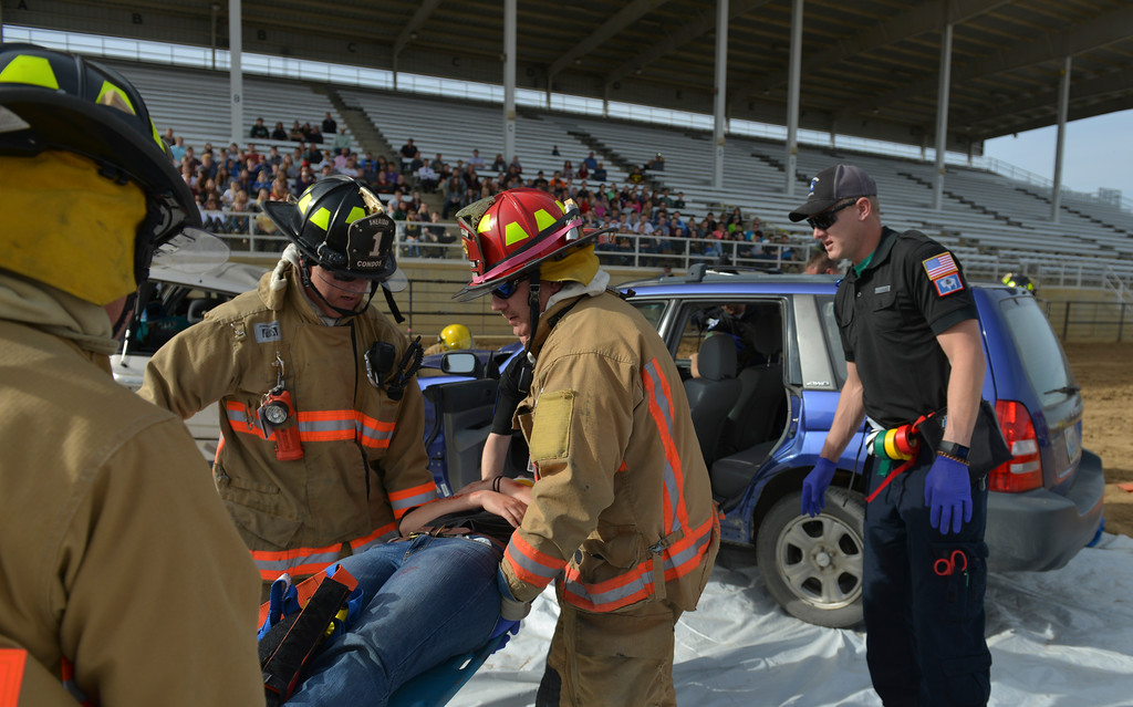 Justin Sheely | The Sheridan Press<br /> Firefighters pull out a student from one of the wrecked vehicles during the Last Call Demonstration Wednesday at the Sheridan County Fairgrounds. Tongue River seniors Sierra McCoy and Kylee Knobloch organized the demonstration for their FCCLA project. Students from Big Horn and Tongue River high schools participated in role playing a scenario of students driving after an underage drinking party collides head-on with another vehicle full of students returning home from a day hiking in the Tongue River Canyon. The scenario was to graphically demonstrate to the student body from Big Horn and Tongue River high schools, the consequences of drunken and distracted driving. Sheridan Fire-Rescue helped organized the demonstration. Agencies in the demonstration included Sheridan County Sheriff's Office, Big Horn and Tongue River Fire Districts, Rocky Mountain Ambulance, Sheridan Police Department and Wyoming Highway Patrol.