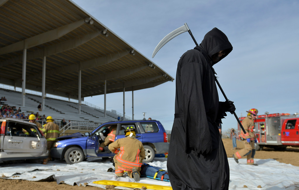 Justin Sheely | The Sheridan Press<br /> The angel of death haunts the scene of a head-on vehicle collision during the Last Call Demonstration Wednesday at the Sheridan County Fairgrounds. Tongue River seniors Sierra McCoy and Kylee Knobloch organized the demonstration for their FCCLA project. Students from Big Horn and Tongue River high schools participated in role playing a scenario of students driving after an underage drinking party collides head-on with another vehicle full of students returning home from a day hiking in the Tongue River Canyon. The scenario was to graphically demonstrate to the student body from Big Horn and Tongue River high schools, the consequences of drunken and distracted driving. Sheridan Fire-Rescue helped organized the demonstration. Agencies in the demonstration included Sheridan County Sheriff's Office, Big Horn and Tongue River Fire Districts, Rocky Mountain Ambulance, Sheridan Police Department and Wyoming Highway Patrol.