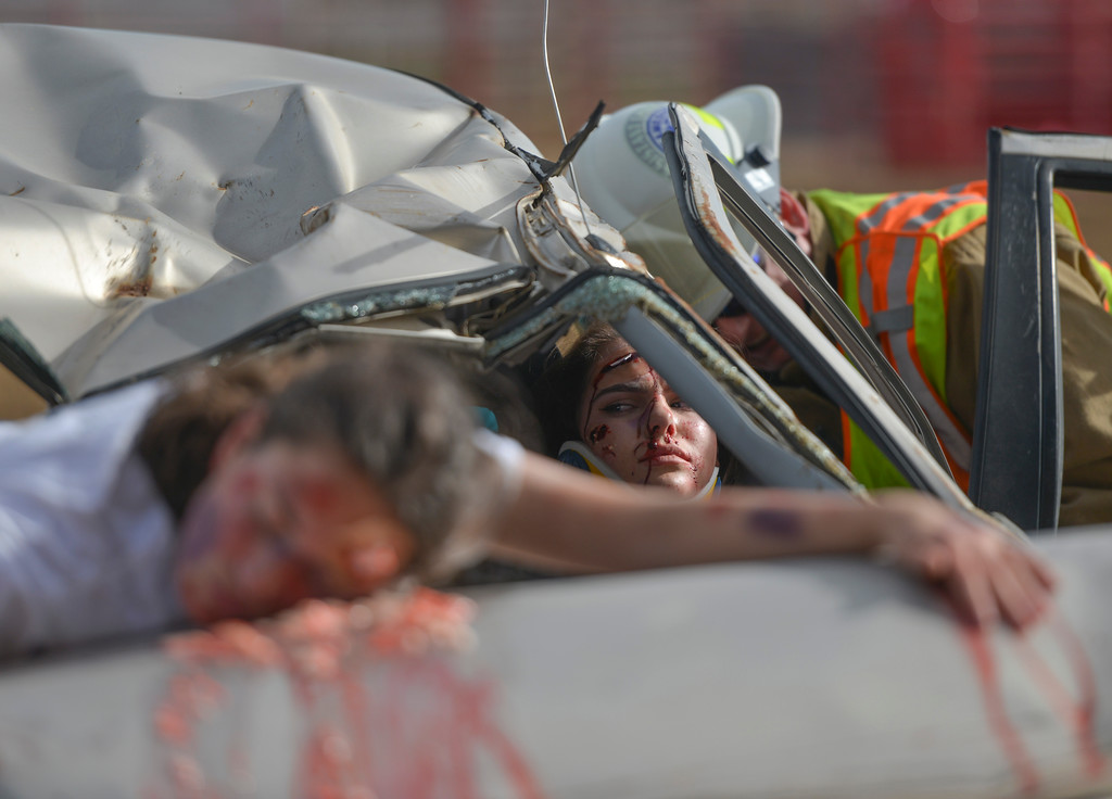 Justin Sheely | The Sheridan Press<br /> Tongue River High School student Anya Wobig looks over at the body of Nikki Perfetti on the hood of the car after a head-on vehicle collision during the Last Call Demonstration Wednesday at the Sheridan County Fairgrounds. Tongue River seniors Sierra McCoy and Kylee Knobloch organized the demonstration for their FCCLA project. Students from Big Horn and Tongue River high schools participated in role playing a scenario of students driving after an underage drinking party collides head-on with another vehicle full of students returning home from a day hiking in the Tongue River Canyon. The scenario was to graphically demonstrate to the student body from Big Horn and Tongue River high schools, the consequences of drunken and distracted driving. Sheridan Fire-Rescue helped organized the demonstration. Agencies in the demonstration included Sheridan County Sheriff's Office, Big Horn and Tongue River Fire Districts, Rocky Mountain Ambulance, Sheridan Police Department and Wyoming Highway Patrol.