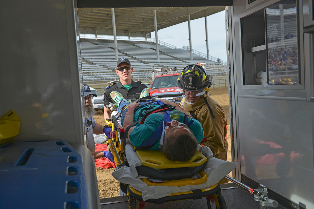 Justin Sheely | The Sheridan Press<br /> Big Horn High School student Cheyna Bradshaw is lifted into an ambulance after a head-on vehicle collision during the Last Call Demonstration Wednesday at the Sheridan County Fairgrounds. Tongue River seniors Sierra McCoy and Kylee Knobloch organized the demonstration for their FCCLA project. Students from Big Horn and Tongue River high schools participated in role playing a scenario of students driving after an underage drinking party collides head-on with another vehicle full of students returning home from a day hiking in the Tongue River Canyon. The scenario was to graphically demonstrate to the student body from Big Horn and Tongue River high schools, the consequences of drunken and distracted driving. Sheridan Fire-Rescue helped organized the demonstration. Agencies in the demonstration included Sheridan County Sheriff's Office, Big Horn and Tongue River Fire Districts, Rocky Mountain Ambulance, Sheridan Police Department and Wyoming Highway Patrol.