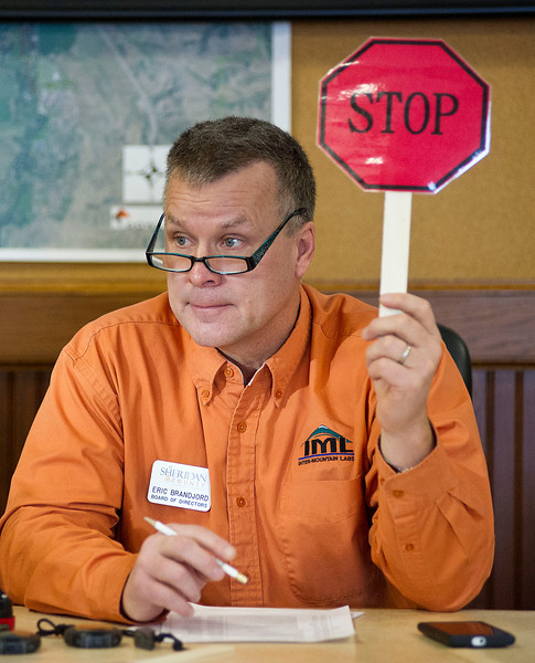 Eric Brandjord raises a sign to signal the room that the speaker's time is done during the Legislative Forum Thursday morning at City Hall. (The Sheridan Press/Justin Sheely)