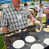 Buffalo Chamber Board Member Jon Williams flips a pancake at the Kiwanis Pancake Breakfast during Longmire Days Saturday at Crazy Woman Square in Buffalo.