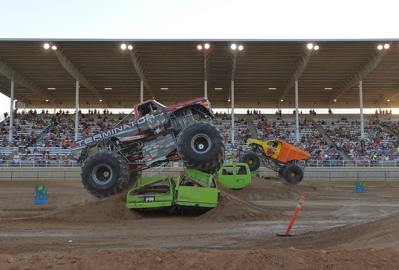 Justin Sheely | The Sheridan Press<br /> Monster trucks race during the Mega Promotions Monster Truck show Saturday at the Sheridan County Fairgrounds.