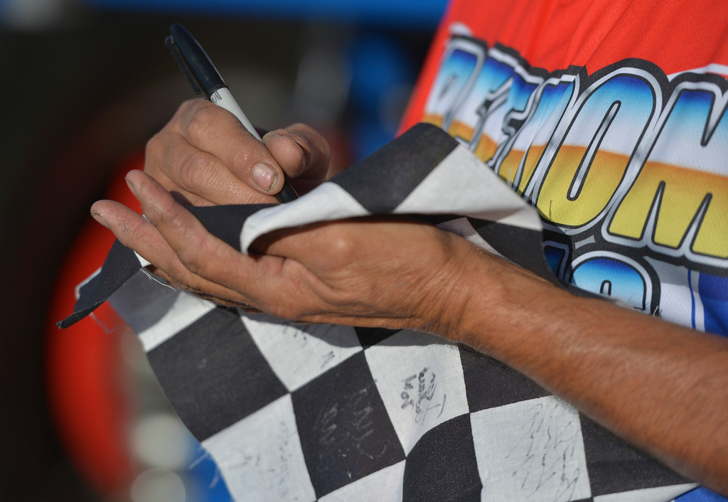 Justin Sheely | The Sheridan Press<br /> A monster truck driver autographs a flag for the VIP pit stop event prior to the Mega Promotions Monster Truck show Saturday at the Sheridan County Fairgrounds.
