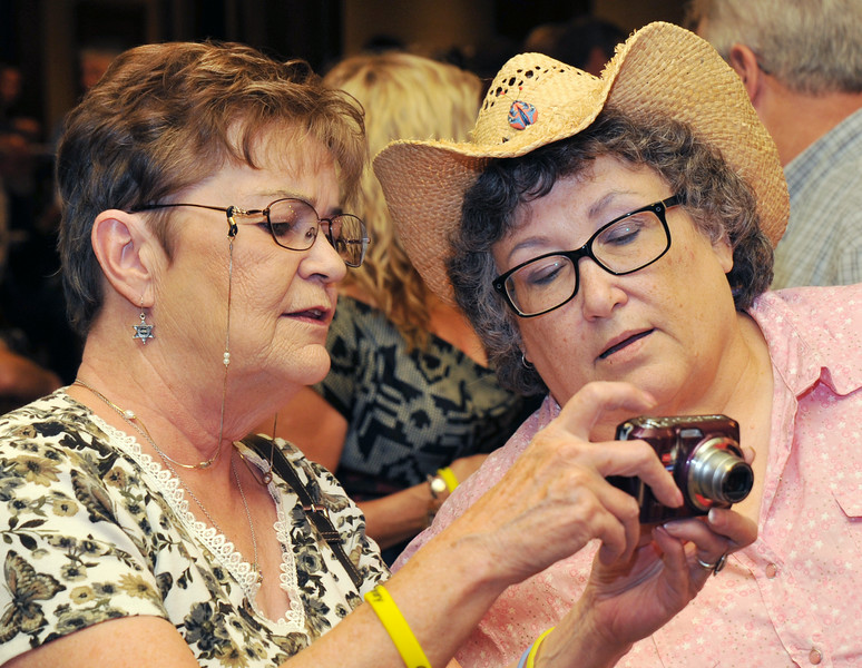 """Linda Hall, left, shows Teri Haley how to operate her camera before meeting Longmire actor Adam Bartley during the 'One Book Wyoming' Longmire event Tuesday evening at the historic Sheridan Inn. The event featured actors from the cable series 'Longmire' and Longmire book series author Craig Johnson. Actor Robert Taylor """"Walt Longmire"""" was scheduled to meet fans but was delayed at the Denver airport. The actors will be meeting fans for Longmire Days in Buffalo this weekend."""