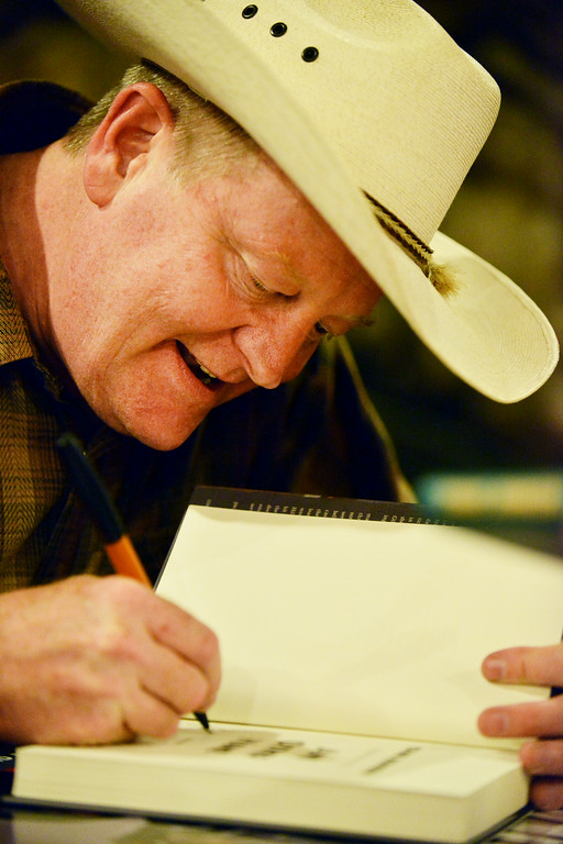 """Local author Craig Johnson autographs one of his books for a fan during the 'One Book Wyoming' Longmire event Tuesday evening at the historic Sheridan Inn. The libraries in Sheridan County are giving away 300 copies of """"Spirit of Steamboat"""" for those interested in the One Book Wyoming program. Book discussions will take place at the libraries in Story, Ranchester, and Sheridan on August 4, 5, and 11, respectively."""