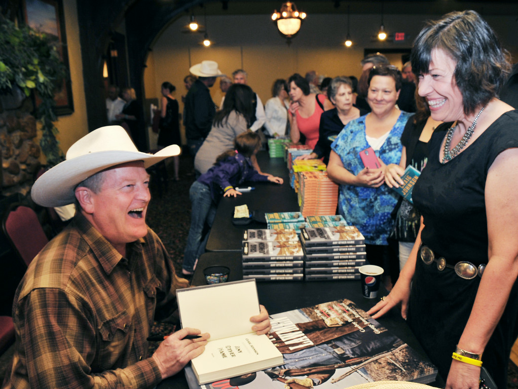 """Local author Craig Johnson autographs his book for Tami Davis during the  'One Book Wyoming' Longmire event Tuesday evening at the historic Sheridan Inn. The libraries in Sheridan County are giving away 300 copies of the book """"Spirit of Steamboat"""" for those interested in the One Book Wyoming program. Book discussions will take place at the libraries in Story, Ranchester, and Sheridan on August 4, 5, and 11, respectively."""