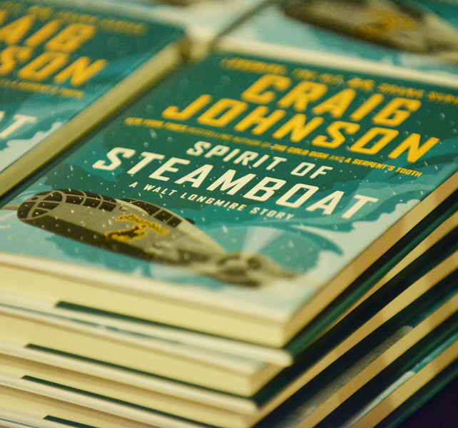 """A stack of """"Spirit of Steamboat"""" books by author Craig Johnson is displayed during the 'One Book Wyoming' Longmire event Tuesday evening at the historic Sheridan Inn. The libraries in Sheridan County are giving away 300 copies of the book for those interested in the One Book Wyoming program. Book discussions will take place at the libraries in Story, Ranchester, and Sheridan on August 4, 5, and 11, respectively."""