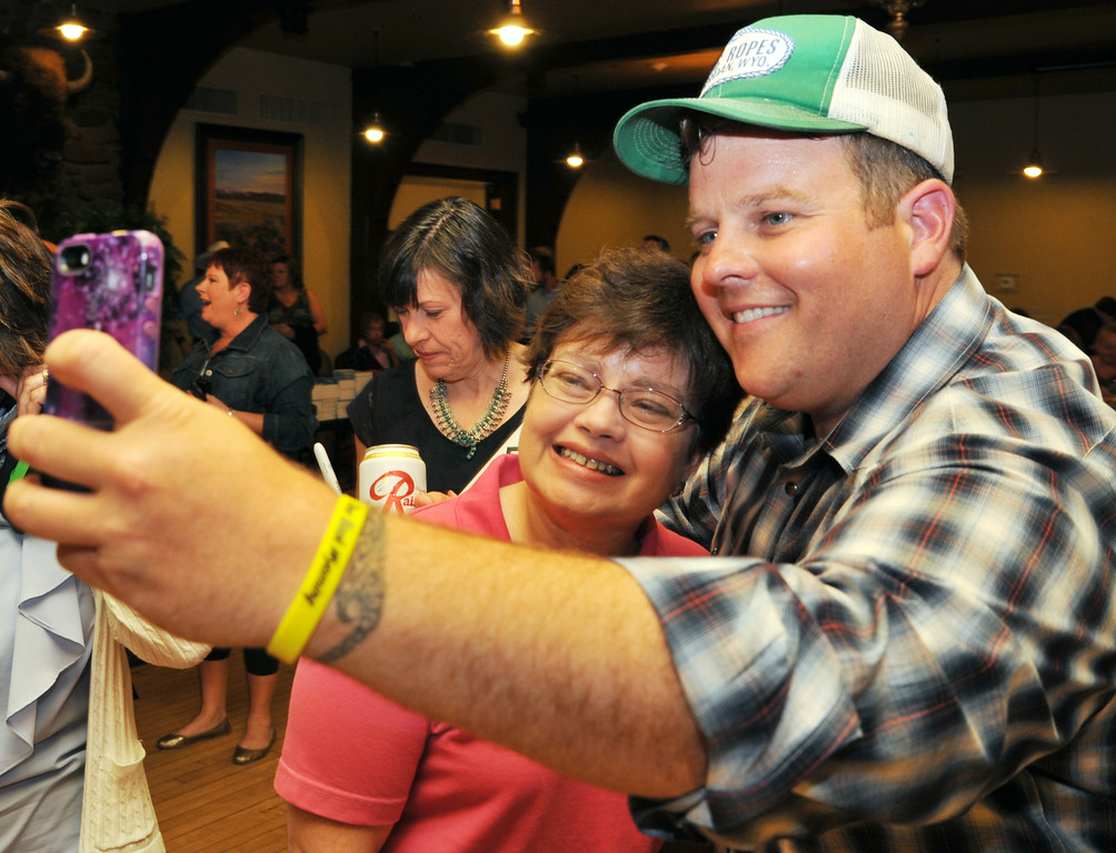 """Georgia Lanham and poses with Longmire actor Adam Bartley for a selfie during the 'One Book Wyoming' Longmire event Tuesday evening at the historic Sheridan Inn. The event featured actors from the cable series 'Longmire' and Longmire book series author Craig Johnson. Actor Robert Taylor """"Walt Longmire"""" was scheduled to meet fans but was delayed at the Denver airport. The actors will be meeting fans for Longmire Days in Buffalo this weekend."""