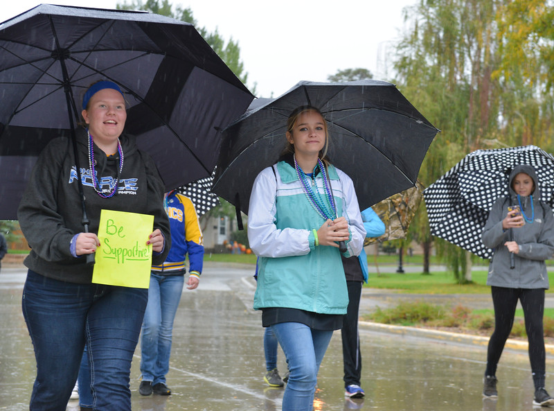 Justin Sheely | The Sheridan Press<br /> Abigail James, left, and Karlee Larson walk in support under pouring rain during the Out of the Darkness suicide prevention walk Saturday in Sheridan. The event is held annually in Sheridan and across the nation by the American Foundation for Suicide Prevention. The walk benefits the AFSP and promotes awareness for suicide prevention and to destigmatize seeking mental help.