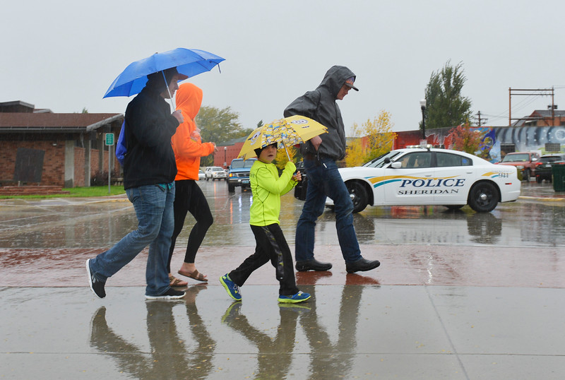 Justin Sheely | The Sheridan Press<br /> A family crosses the street under pouring rain during the Out of the Darkness suicide prevention walk Saturday in Sheridan. The event is held annually in Sheridan and across the nation by the American Foundation for Suicide Prevention. The walk benefits the AFSP and promotes awareness for suicide prevention and to destigmatize seeking mental help.