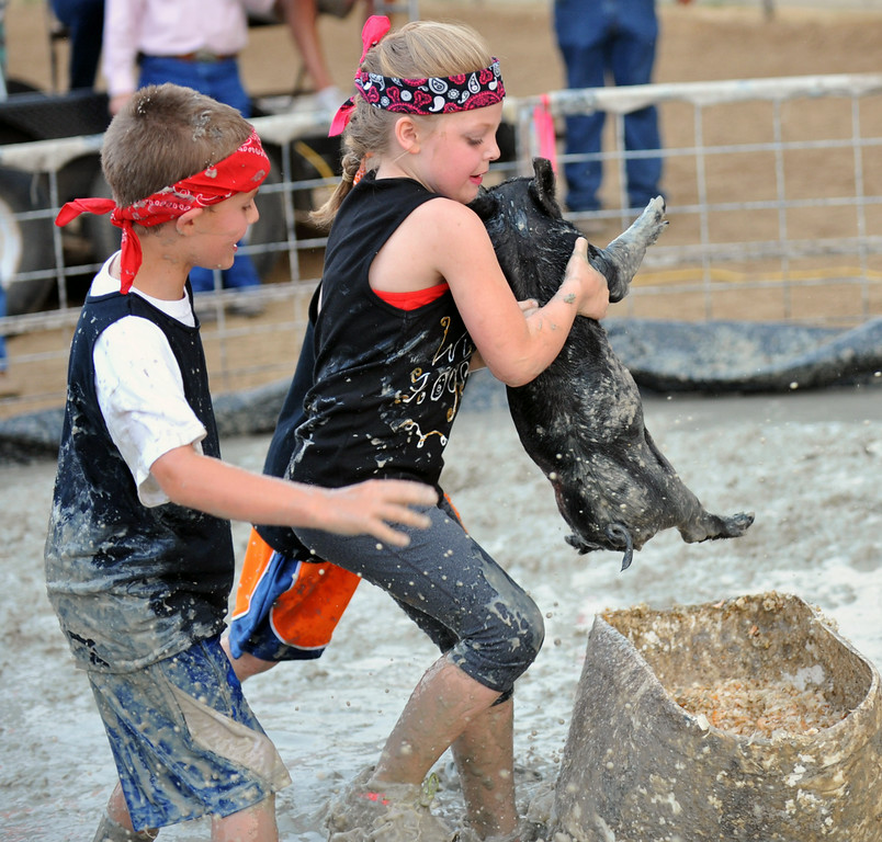 The Wild Hogs Pee Wee team carries their pig to the bucket Sunday night at the pig wrestling tournament. Pictured from left to right: Ty Leach and Chelsee Morris, both age seven. The Sheridan Press/Kendra Cousineau