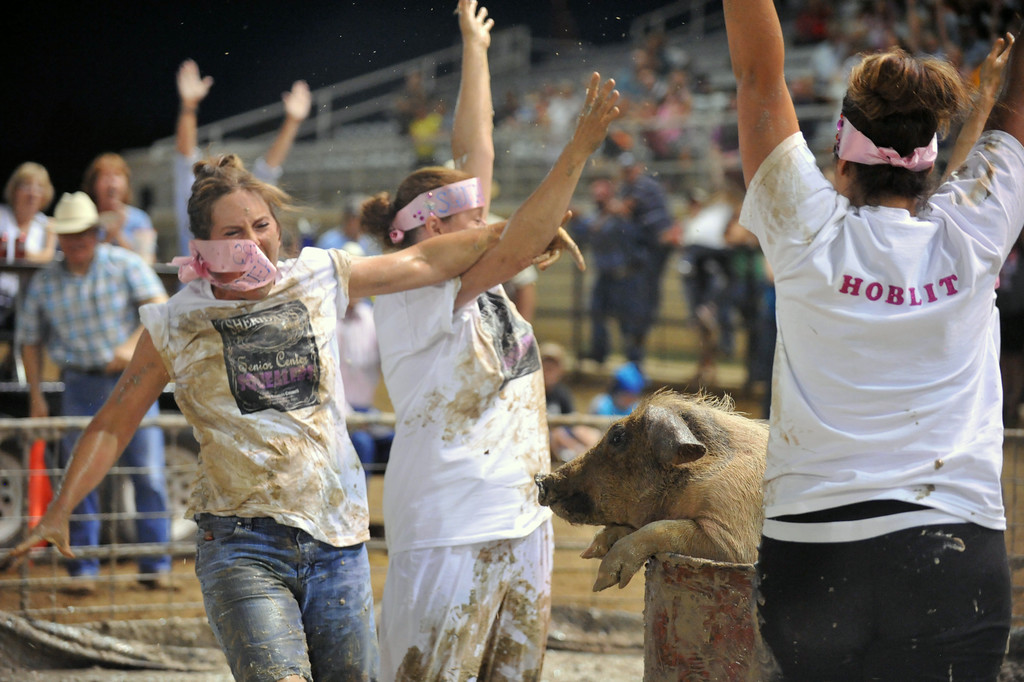 The Squealers celebrate getting the pig into the bucket Sunday night. The Sheridan Press/Kendra Cousineau