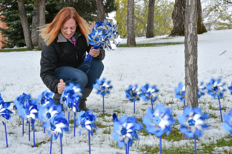 "Justin Sheely | The Sheridan Press<br /> Amanda Dube with the Child Developement Center places pinwheels during ""Pinwheels for Justice"" pinwheel garden project Wednesday at the Sheridan County Courthouse. Sheridan County Public Health and Compass hosted the project to raise awareness and on child abuse and neglect. Funds raised from the pinwheel garden benefit education programs at Prevent Child Abuse Wyoming."
