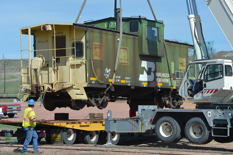 Justin Sheely | The Sheridan Press<br /> A 53,000-lbs caboose is carefully lowered by crane onto a flatbed Friday morning in Ranchester. The 40-year-old Burlington Northern caboose was donated to the town of Ranchester by BNSF to be displayed by town hall in Ranchester. The caboose had to be lifted from the tracks by crane and transported by truck to its new home.