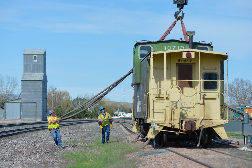 Justin Sheely | The Sheridan Press<br /> BNSF workers pull straps around 53,000-lbs caboose Friday morning in Ranchester. The 40-year-old Burlington Northern caboose was donated to the town of Ranchester by BNSF to be displayed by town hall in Ranchester. The caboose had to be lifted from the tracks by crane and transported by truck to its new home.