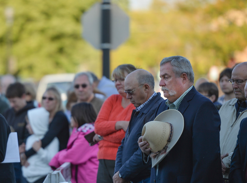 Justin Sheely | The Sheridan Press<br /> Community members pause as the invocation is led by Reverend John Meyer during the remembrance ceremony on the 15-year anniversary of 9/11 Sunday at Sheridan Fire-Rescue. Firefighters, law enforcement, EMT and other emergency agencies observed a minute of silence in reflection of the lives lost during the Sept. 11, 2001 terrorist attacks. Sheridan Fire-Rescue also unveiled a bronze statue made in the likeness of Sheridan Fire Department firefighter Capt. Ed Green holding a firehose while battling a lumber yard fire in 1979. Green died of cancer in 2007.