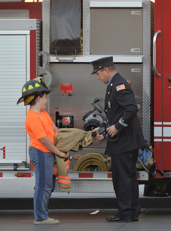 Justin Sheely | The Sheridan Press<br /> Gage Neeson helps his dad George Neeson setting out firefighter gear next to a fire engine prior to the remembrance ceremony on the 15-year anniversary of 9/11 Sunday at Sheridan Fire-Rescue. Firefighters, law enforcement, EMT and other emergency agencies observed a minute of silence in reflection of the lives lost during the Sept. 11, 2001 terrorist attacks. Sheridan Fire-Rescue also unveiled a bronze statue made in the likeness of Sheridan Fire Department firefighter Capt. Ed Green holding a firehose while battling a lumber yard fire in 1979. Green died of cancer in 2007.