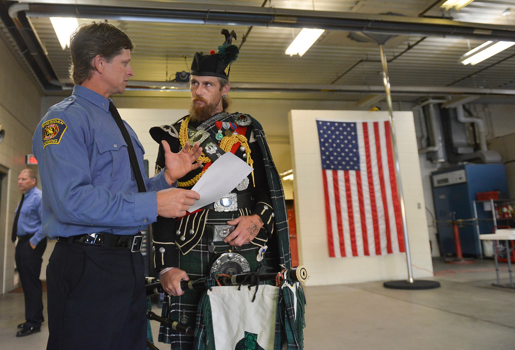 Justin Sheely | The Sheridan Press<br /> Sheridan firefighter Chad Brutlag, left, runs over the order of ceremony with bagpipe player Rob MacLean prior to the remembrance ceremony on the 15-year anniversary of 9/11 Sunday at Sheridan Fire-Rescue. Firefighters, law enforcement, EMT and other emergency agencies observed a minute of silence in reflection of the lives lost during the Sept. 11, 2001 terrorist attacks. Sheridan Fire-Rescue also unveiled a bronze statue made in the likeness of Sheridan Fire Department firefighter Capt. Ed Green holding a firehose while battling a lumber yard fire in 1979. Green died of cancer in 2007.