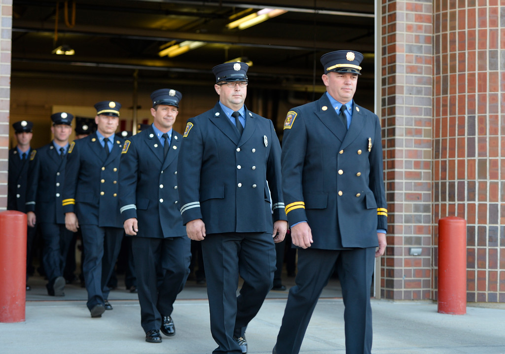 Justin Sheely | The Sheridan Press<br /> Firefighters exit the bay door to stand at attention during the remembrance ceremony on the 15-year anniversary of 9/11 Sunday at Sheridan Fire-Rescue. Firefighters, law enforcement, EMT and other emergency agencies observed a minute of silence in reflection of the lives lost during the Sept. 11, 2001 terrorist attacks. Sheridan Fire-Rescue also unveiled a bronze statue made in the likeness of Sheridan Fire Department firefighter Capt. Ed Green holding a firehose while battling a lumber yard fire in 1979. Green died of cancer in 2007.
