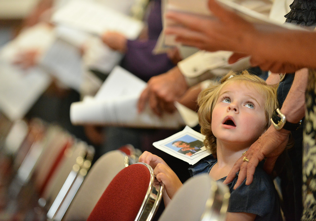 3-year-old Ciera Reculusa of Kaycee looks up at her grandmother as guests sing a hymn during the Celebration of Life service of Sen. John Schiffer, R–Kaycee, at the Kaycee High School gymnasium in Kaycee, Wyo. Attendance for the service contained a mix of family, friends, neighbors, colleagues, politicians, and other dignitaries. Sen. John Schiffer died last week at age 68 from liver cancer. The Sheridan Press|Justin Sheely.