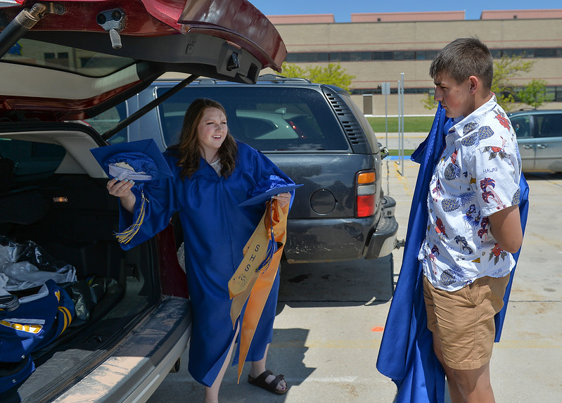 Justin Sheely | The Sheridan Press<br /> Tayci Maxwell and Derek Vela put on their garments in the parking lot prior to the 2017 graduation ceremony Saturday at Sheridan High School.