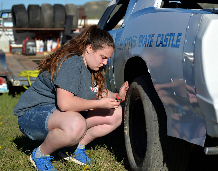 Justin Sheely | The Sheridan Press<br /> Seventeen-year-old Abagail Chavez checks the tire pressure on her dad's IMCA hobby stock car in the track pit during the opening race day for the season Friday at Sheridan Speedway. Chavez said she wants to be her own driver when she can raise the money to build her own race car. Dirt track racing is has been a long-held favorite summer activity for Sheridan spectators, drivers and organizers. The site reopened in spring of 2015 after being vacant for five years. This month's racing schedule is set on Friday, May 12 and 19, and Thursday, May 25.