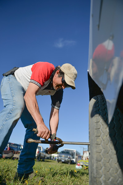Justin Sheely | The Sheridan Press<br /> Adrian Chavez checks the lug nuts on his brother's car in the track pit during the opening race day for the season Friday at Sheridan Speedway. Dirt track racing is has been a long-held favorite summer activity for Sheridan spectators, drivers and organizers. The site reopened in spring of 2015 after being vacant for five years. This month's racing schedule is set on Friday, May 12 and 19, and Thursday, May 25.