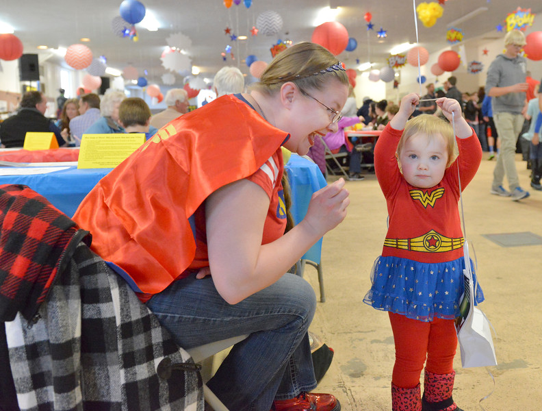 "Justin Sheely | The Sheridan Press<br /> Sara Haight and her daughter Miranda Haight, 2, dressed as Wonder Woman for the ""Souper Hero"" theme this year during the ""Filling and Empty Bowl"" VOA soup fundraiser at the Sheridan County Fairgrounds Exhibit Hall. The annual event supports homeless services in Sheridan operated by Volunteers of America of the Northern Rockies."