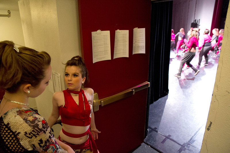 Tori Huston, right, looks at Olivia Boley as they watch their peers perform onstage.
