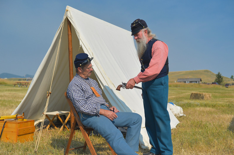 Justin Sheely | The Sheridan Press<br /> Historic actors Craig Fischer of Colorado, left, looks at a 1851 Navy Colt .36 Cal. revolver from Dennis Borud of Montana Friday morning in the encampment at the Fort Phil Kearny State Historic Site. The encampment will be open throughout the weekend for visitors. The state park will host a reenactment of the Wagon Box Fight Saturday at noon. Tickets are available at the office at the historic site.