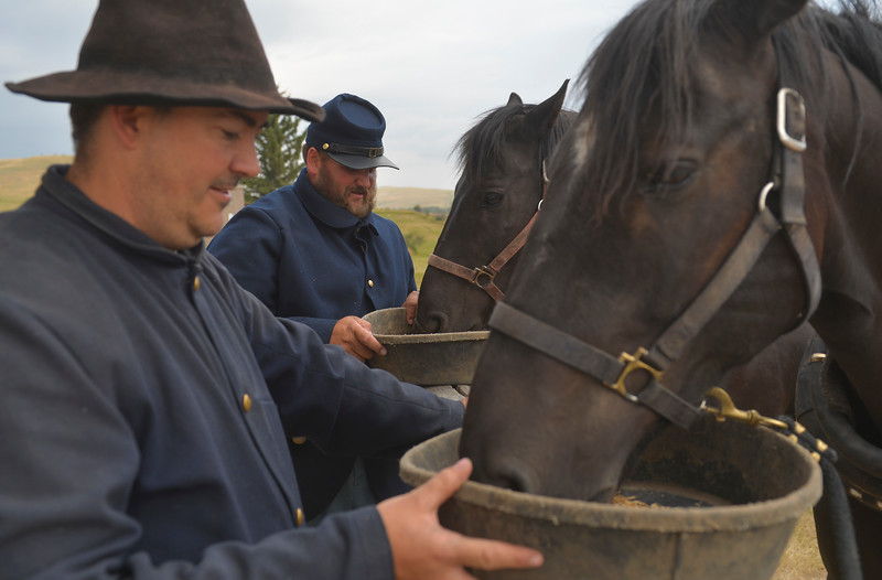 Justin Sheely | The Sheridan Press<br /> Members of the Fort Phil Kearny Regulars George Mediate, left, and Spencer Morris feed their team horses before hitching the wagon for the reenactment battle during the 150-year anniversary of the Wagon Box Fight Saturday at the Fort Phil Kearny State Historic Site. The battle involved 32 United States soldiers and nearly 800 warriors on Aug. 2, 1867 approximately 30 miles south of Sheridan. The soldiers held off the attacks of the Native warriors with only six casualties.