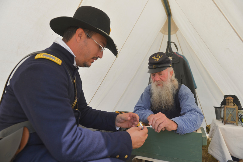 Justin Sheely | The Sheridan Press<br /> Reenactor Erik Holloway, left, looks at musket ammo made by Dennis Borud prior to the reenactment battle during the 150-year anniversary of the Wagon Box Fight Saturday at the Fort Phil Kearny State Historic Site. The battle involved 32 United States soldiers and nearly 800 warriors on Aug. 2, 1867 approximately 30 miles south of Sheridan. The soldiers held off the attacks of the Native warriors with only six casualties.