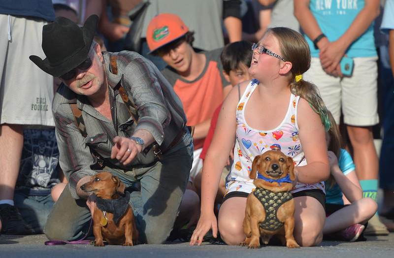 Justin Sheely | The Sheridan Press<br /> Dennis Howard, left, and Hailey McGee, 12, hold their dogs at the starting line during the Wiener Dog Races Tuesday evening outside of Black Tooth Brewery. The event was hosted by Muddy Paw Prints.