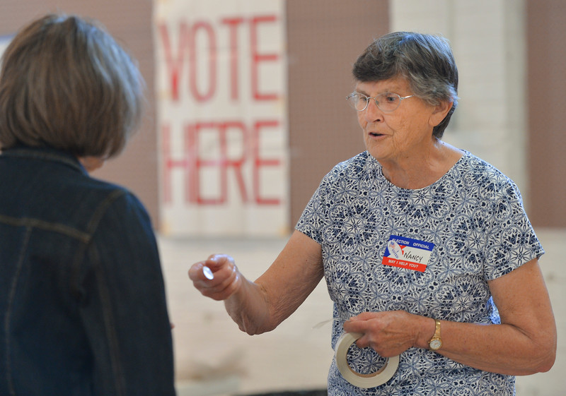 Justin Sheely | The Sheridan Press<br /> Election official Nancy Laughrey offers a sticker after a resident votes during the Wyoming Primary Election Tuesday at the Sheridan County Fairgrounds Exhibit Hall.