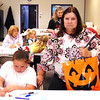 Ellie Snapp, 8, Morris, colors a Halloween rainbow bookmark while grandmother Stephanie Meyer, Batesville, watches at Tri-State Artisans. Meyer holds a goodie bag from Aunt Bea's Gifts.