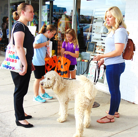 Batesville sisters Brooke (left) and Brianna Ballard keep an eye on goldendoodle Teddy, 10 months, while Brooke's daughters, Riley, 9, and Aubrey, 8, compare items inside goodie bags from Aunt Bea's Gifts.