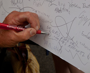 """God Bless America"". Charles Minkowitz signs a poster of the Declaration of Independence."