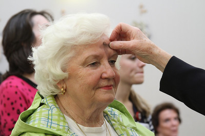 Louisa Alexander, a parishioner at Our Lady of the Assumption Church, Atlanta, receives ashes during Mass at the St. Joseph's Hospital chapel.