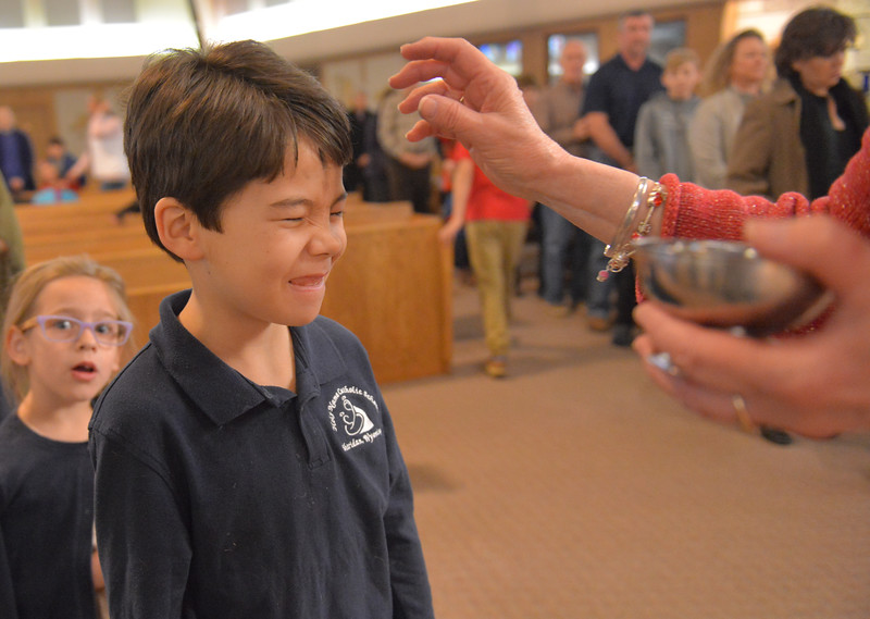 Justin Sheely | The Sheridan Press<br /> <br /> Second-grader Jackson Peterson squints as he receives the mark of ashes with Lillian Fort looking on during morning mass at Holy Name Catholic Church on Ash Wednesday, Feb. 14, 2018. Ash Wednesday marks the beginning of a 40-day season of Lent.
