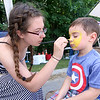 Liam Walker, 3, sits very still as he gets his face painted by Seana Mawhinney, 17, both of Ashburnham during the Inaugural Ashburnham Lion's Club Community Day on Saturday. SENTIENL & ENTERPRISE/JOHN LOVE