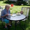 Grannie and Eve having lunch in the garden.  Eve has just been told to smile.