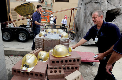 Ryan Thorpe, right, and  Brian Hunter, paint mining helmets with hospital staff  that work on the Avista entry for the parade on Monday. Avista Adventist Hospital is again pulling out all the stops in creating their float for the Louisville Labor Day Parade. For a video and photos of the float, go to www.dailycamera.com. Cliff Grassmick / September 1, 2011