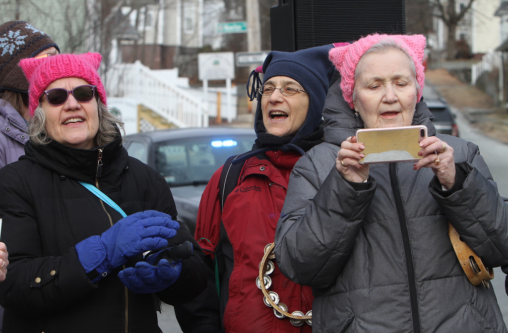 . Women\'s March in Ayer begins with a rally at Town Hall. From left, Anna Fadden of Ayer, Sherry Zitter of Maynard and Caroline Marvin of Littleton, members of the Unitarian Universalist Voices for Justice, who sang. (SUN/Julia Malakie)
