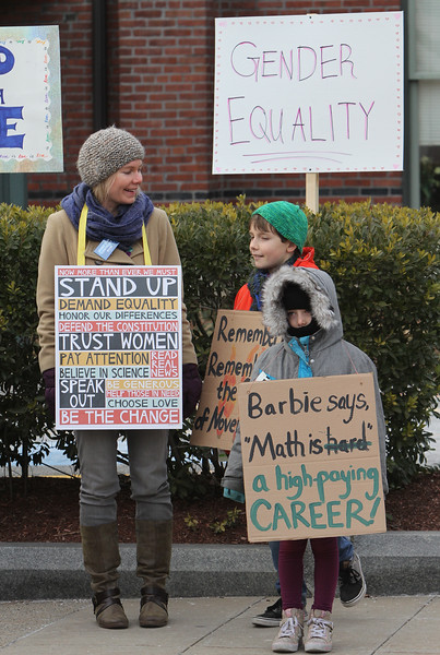 Women's March in Ayer begins with a rally at Town Hall. Katy Covino, left, with son Russell Poutasse, 11, and daughter Flora Poutasse, 6. (SUN/Julia Malakie)