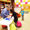 "Vicki Kruse (from left), Batesville, and granddaughter Monroe Phillips, 9, Indianapolis, dress paper dolls while Zach Marcy, 5, Batesville watches. Note the farmscape and vivid squares on the walls and playhouse in the background. Library director Kim Porter says she wants the renovated area to be where ""families want to be and kids are excited to come. I want it to be a fun place."""