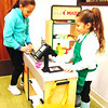 Sisters Kassandra (left), 8, and Nicole Garza, 5, pretend to be a grocery shopper and cashier in the library's refreshed children's area during the open house.