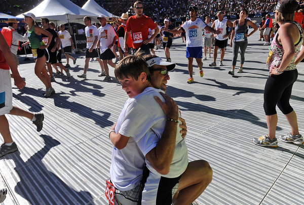 BOLDER<br /> Andrew Davison of Boulder hugs his son, Miller, 8, after they finished the 32nd Annual Day Bolder Boulder on Monday.<br /> Photo by Marty Caivano/Camera/May 31, 2010