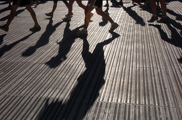BOLDER<br /> Early morning runners cast their shadows on the floor of Folsom Field during the 32nd Annual Day Bolder Boulder on Monday.<br /> Photo by Marty Caivano/Camera/May 31, 2010